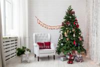 Svetlé kreslo ušiak s červenými dekoračnými vankúšmi a vianočným stromčekom v škandinávskom štýle