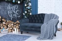 Vintage pohovka so sivou dekou a vianočnými dekoráciami