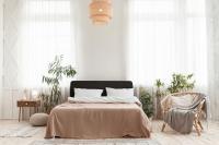 Pohodlná posteľ a ratanové kreslo s dekou vo veľkej spálni