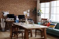 Drevený stôl v pracovni s tehlovou stenou