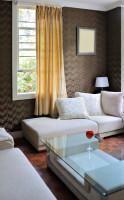 Svetlá pohovka a konferenčný stolík v kontraste s hnedou stenou