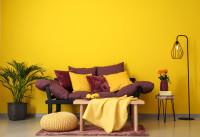 Tmavá pohovka v kontraste so žltou stenou