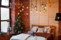 Drevená manželská posteľ s dekoračnými vankúšmi a malý vianočný stromček