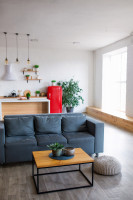 Drevený stolík a sivá pohovka v škandinávskom štýle