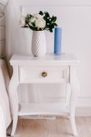 Romantický biely nočný stolík s dekoráciami