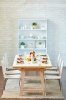 Dlhý jedálenský stôl a drevené stoličky v jedálni s bielou tehlovou stenou