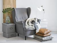Relaxačný kút so sivým kreslom a bielou  stolovou lampou