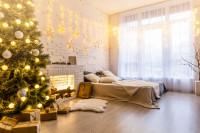 Veľká manželská posteľ v priestrannej spálni s vianočnými dekoráciami