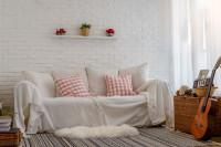 Biela pohovka v boho obývačke s tehlovou stenou