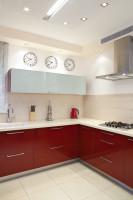 Moderná kuchynská linka s červenými dvierkami a bielou pracovnou doskou