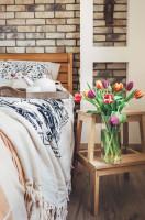 Manželská posteľ a váza s kvetmi v spálni s tehlovou stenou