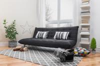 Sivá látková pohovka s dekoračnými vankúšmi vo svetlej škandinávskej obývačke