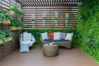Ratanová záhradný nábytok na terase so zelenou stenou