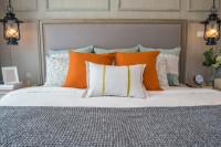 Manželská posteľ s dekoračnými vankúšmi a vintage lampami