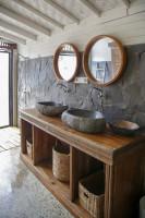 Kamenné umývadlá a drevený nábytok v bohémskej kúpeľni