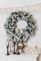 Vianočný veniec s bielymi dekoráciami a čiernymi svietnikmi
