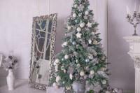 Veľké barokové zrkadlo a vianočný stromček s bielymi a a striebornými ozdobami