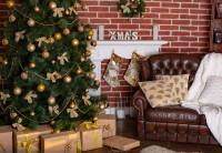 Hnedá kožená pohovka a vianočný stromček so zlatými ozdobami