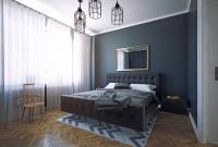 Čalúnená posteľ v spálni s tmavomodrými stenami