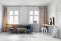 Sivá pohovka vo svetlej obývačke s pracovným kútom