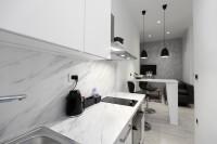 Úzka biela kuchyňa s čiernymi doplnkami