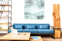 Modrá pohovka a kovový regál s drevenými doplnkami