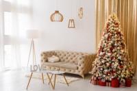 Béžová pohovka so sadou konferenčných stolíkov a vianočným stromčekom so zlatými doplnkami