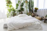 Manželská posteľ v bielej bohémskej spálni s rastlinami