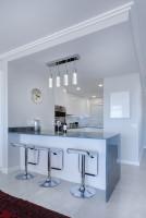 Dizajnové barové stoličky v modernej bielej kuchyni