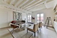 Sivá pohovka v priestrannej bielej obývačke