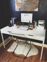 Biely písací stôl v kontraste s tmavomodrou stenou