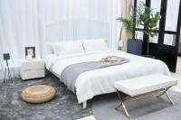 Biela manželská posteľ a čalúnená lavica