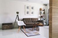 Sivohnedá pohovka vo svetlej škandinávskej obývačke
