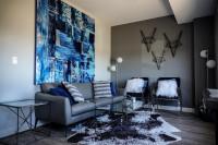 Sivá pohovka a kovové stolíky v modernej obývačke