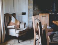 Sivé kreslo ušiak a drevené jedálenské stoličky