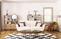 Dvojmiestna biela pohovka, svetlohnedé kreslo a okrúhly konferenčný stolík
