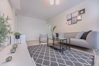 Sivý gauč, sivo-biely koberec a biele skrinky