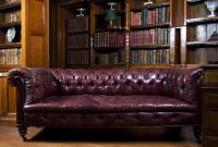 Bordový kožený gauč v knižnici