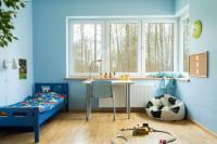 Modrá drevená posteľ, nástenná aj stolová lampa, písací stolík, stolička, sedací vak