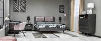 Spálňa zariadená nábytkom v tmavých farbách s retro nádychom
