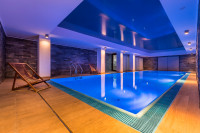 Bazén s drevenou podlahou a lehátkami