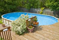 Oválny bazén pri drevenej terase v záhrade