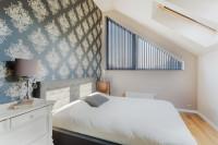 Manželská posteľ so sivým záhlavím, biela komoda a stolová lampa