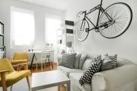 Biela pohovka, žlté kreslá a zavesený bicykel