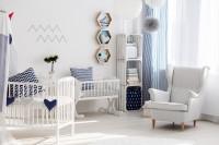 Detská postieľka, kolíska a biely ušiak v izbe ladenej do modra