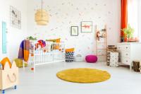Biela postieľka a komoda so šuplíkmi, žltý okrúhly koberec