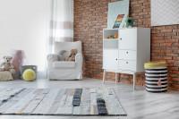 Biele kreslo, biela skrinka so šuplíkmi a koberec