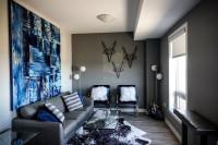 Sivá sedačka s modrými vankúšmi a modrá maľba