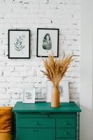 Zelená komoda a fotorámiky na bielej tehlovej stene