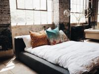 Veľká čalúnená manželská posteľ v industriálnej spálni